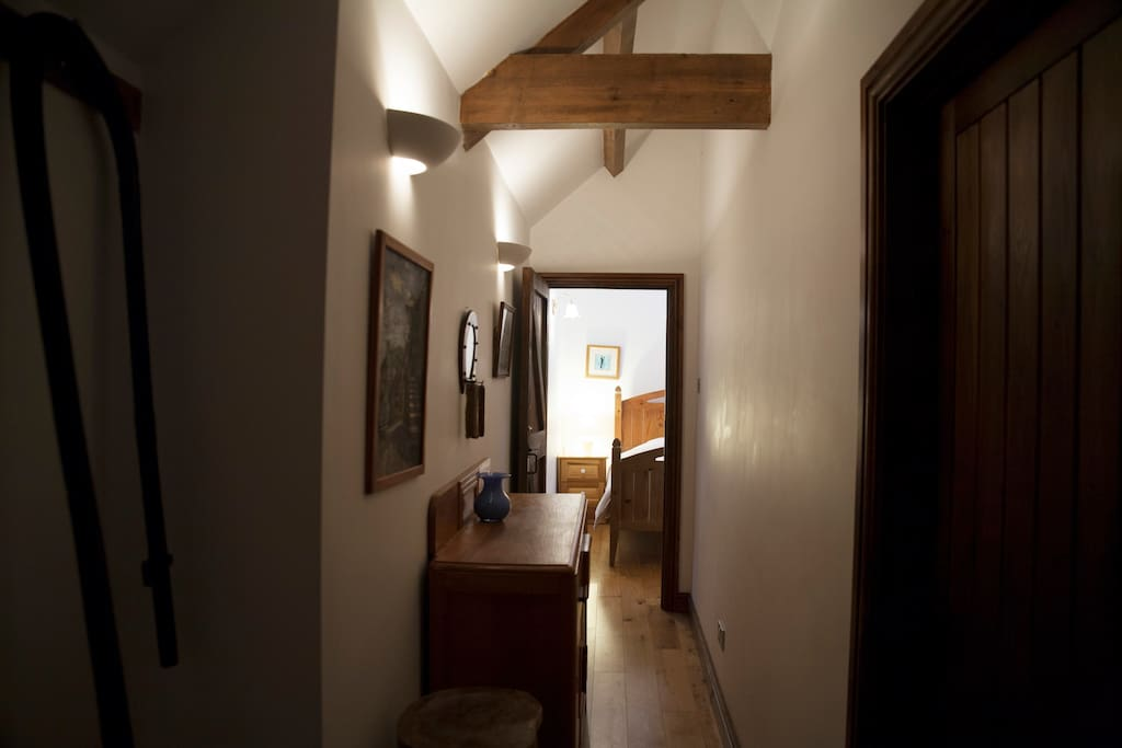 Joining hallway between bedroom and lounge with kitchen to the side all with hardwood floors