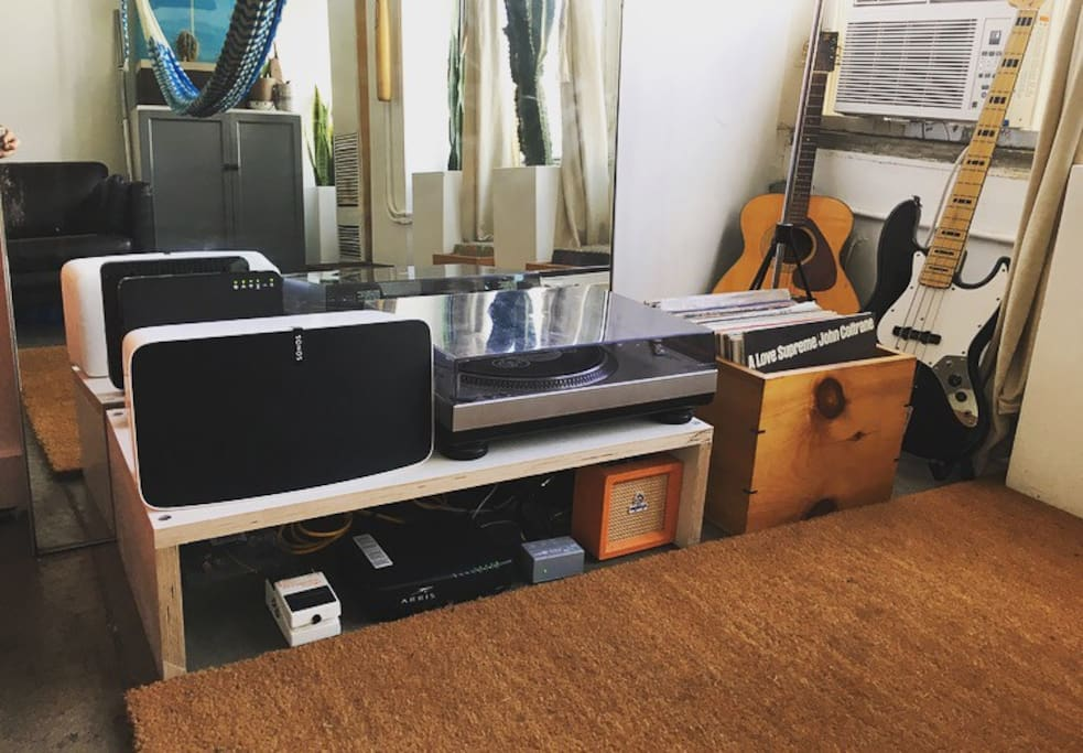 Sonos sound system with record player, collection and guitars