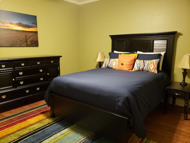 Queen bedroom with storage dresser and large closet
