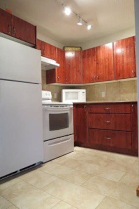 Kitchen with stove, fridge, microwave