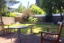 Shaded backyard with patio, lawn chairs, briquette BBQ, and croquet set.