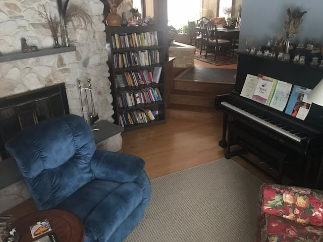 The cozy and comfortable piano room is available for guests to use.  It has a two-way fireplace and large window looking out onto the flower beds and front of property.