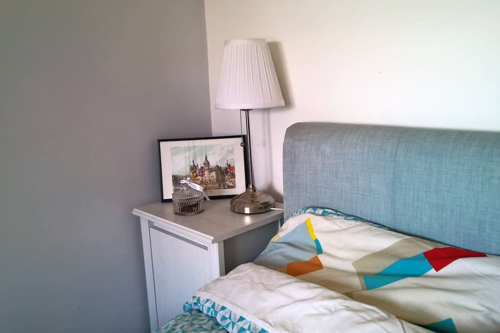 Modern bedside table and lamp, double bed, bright room, lots of storage space.