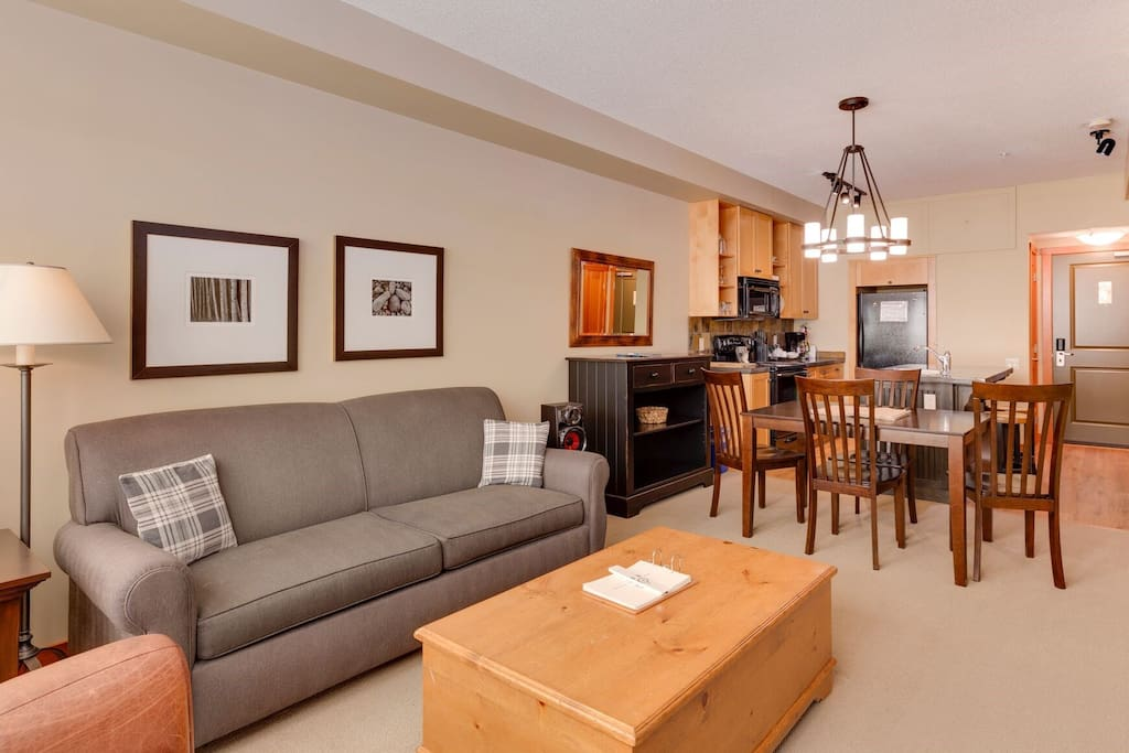 The living space is bright and open, featuring a sitting area, a dining table, and a TV.