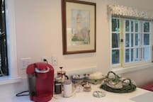 Homemade snacks, Keurig machine and French press.  Tea is in the cupboard by the stove, milk in the fridge.