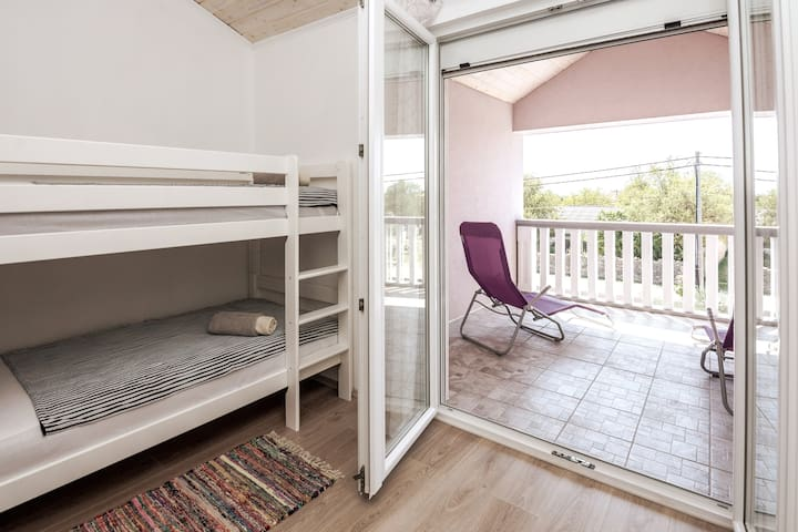 3rd upstairs bedroom. One bunk bed, one single bed,  balcony overlooking the pool, shelves for storage and a clothing rack.