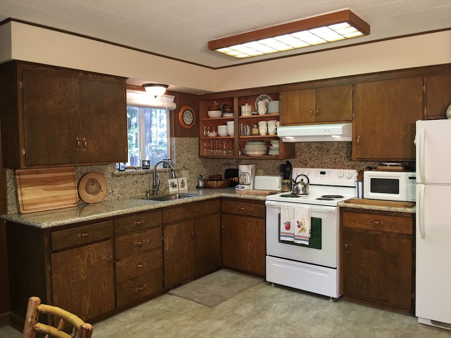 Kitchen with new counter tops and fully stocked with cooking utensils (pots, pans, plates etc.)