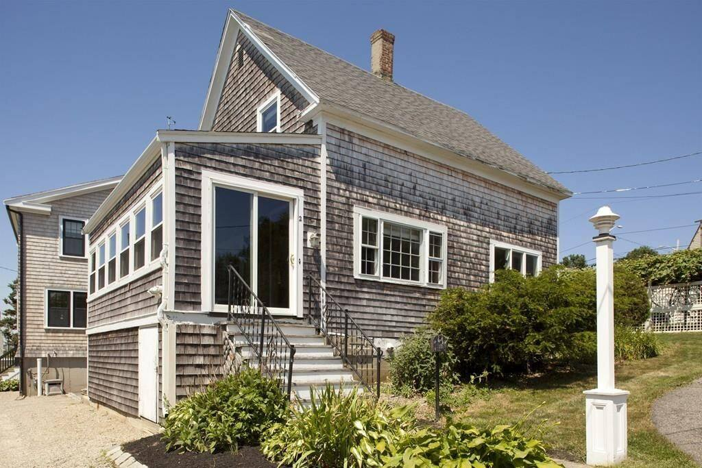 Side of house, including 3 season porch with window views facing bay water