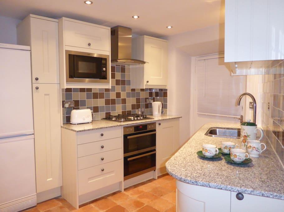 The kitchen has granite worktops, gas hob, double oven, microwave, dishwasher and fridge/freezer