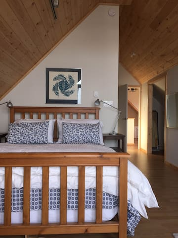 comfortably appointed upper waterfront master bedroom with deep queen bed.