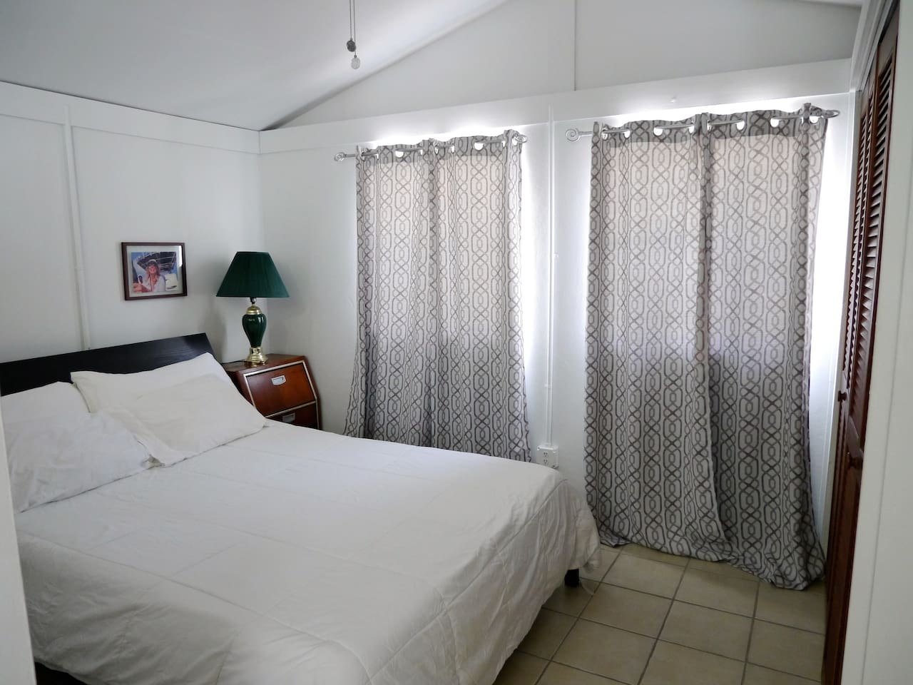 Large double windows feature blinds and heavy drapes for privacy.