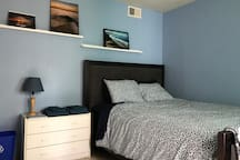 The cozy San Diego Blue Room features a comfortable queen sized bed with photos and reading materials about San Diego.
