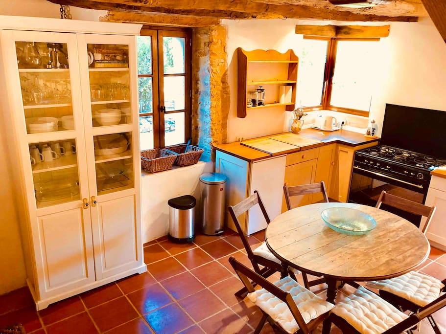 Fully equipped kitchen, with table seating 6 and windows and doors to terrace and garden.