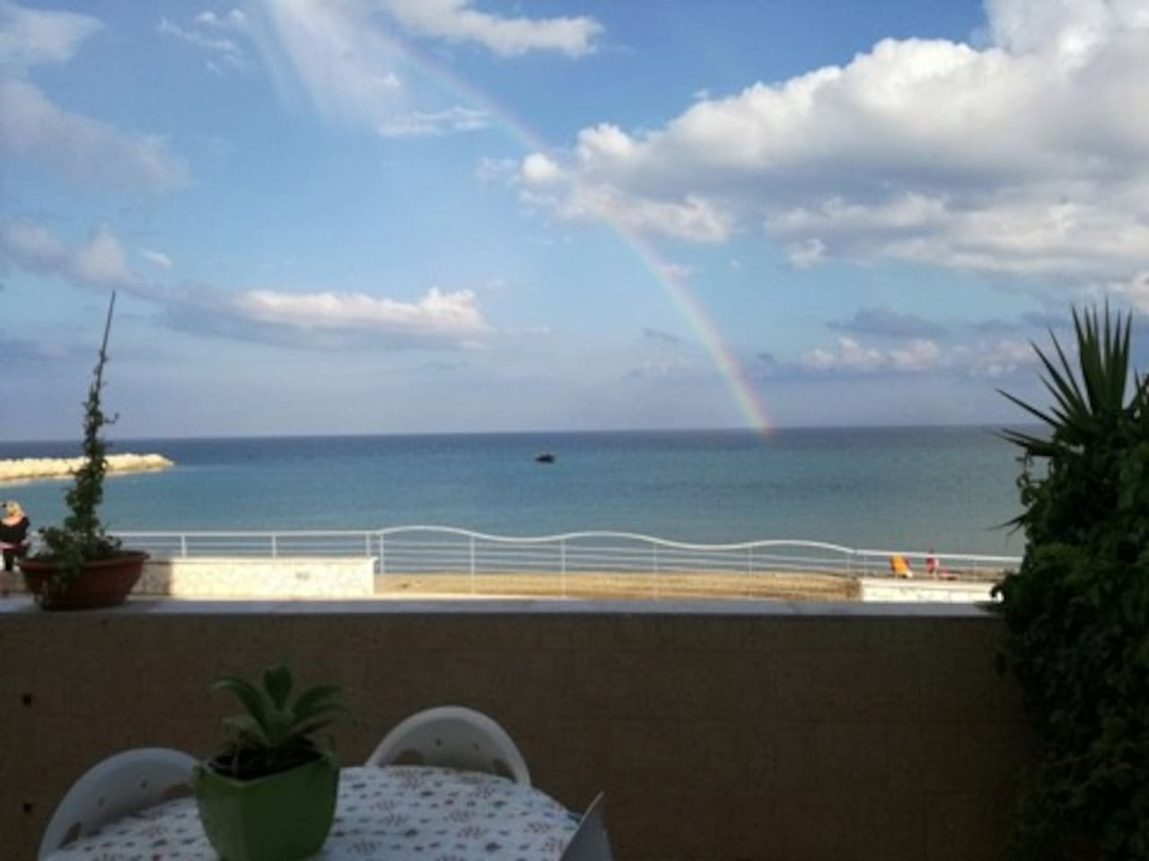 The vieu from the terrace with walking path , the sea and a rainbow
