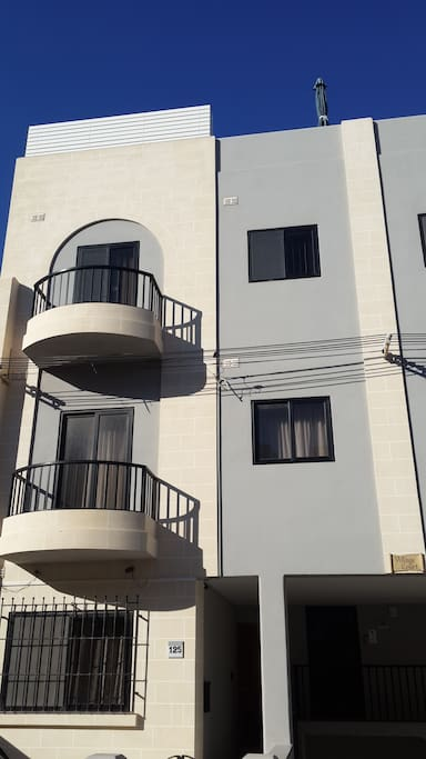 Main Facade of apartment, top floor with front balcony and window.
