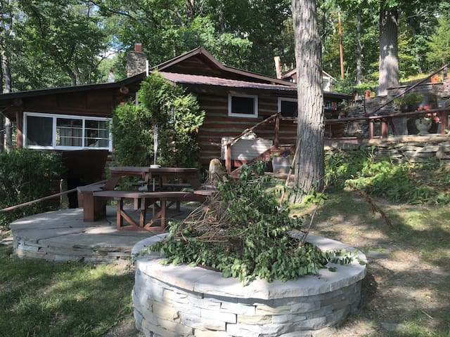 Side view of cabin with round picnic table and fire pit.