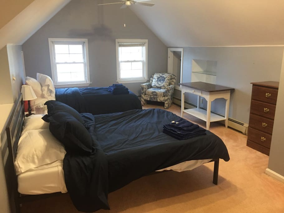 Top floor has two beds, a twin and a queen, as well as a private bathroom with a shower. Computer desk not pictured.