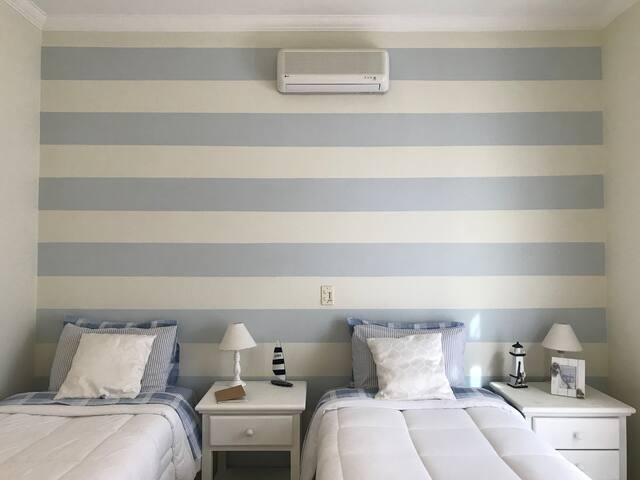 Suíte do Andar térreo, com três camas de solteiro, ar condicionado tipo split e varanda com vista para o jardim dianteiro.