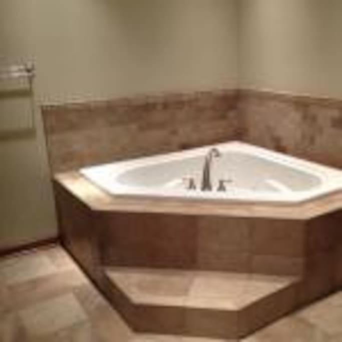 Has a not cheesy Jetted Heart Shaped bath tub.  It also has a big walk in overhead shower along with a washer and dryer - so you don't need to leave with stinky clothes.