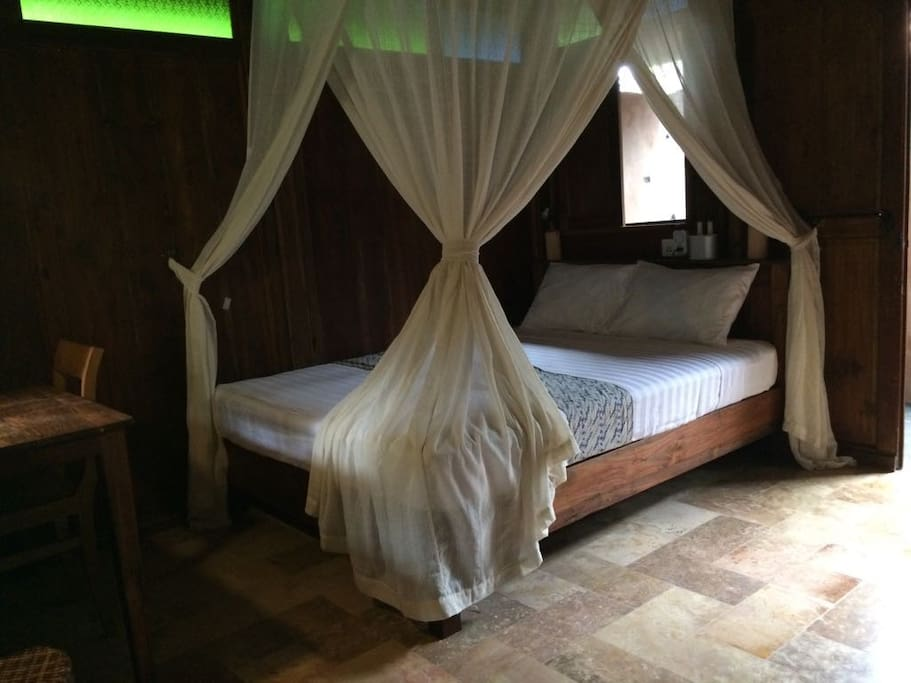 Custom teak wood bed with custom comfy mattress, equipped with cotton handwoven mosquito net.