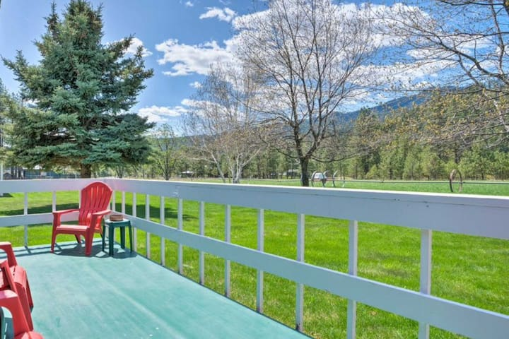 The back deck and chairs offer a view of the property's acerage and surrounding mountains.