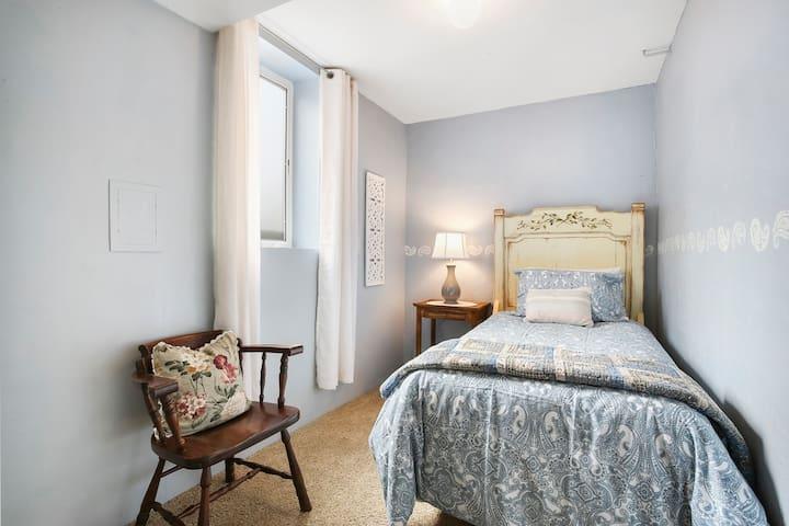 Bedroom #2 has a charming single bed; while natural light brightens the shabby chick style.