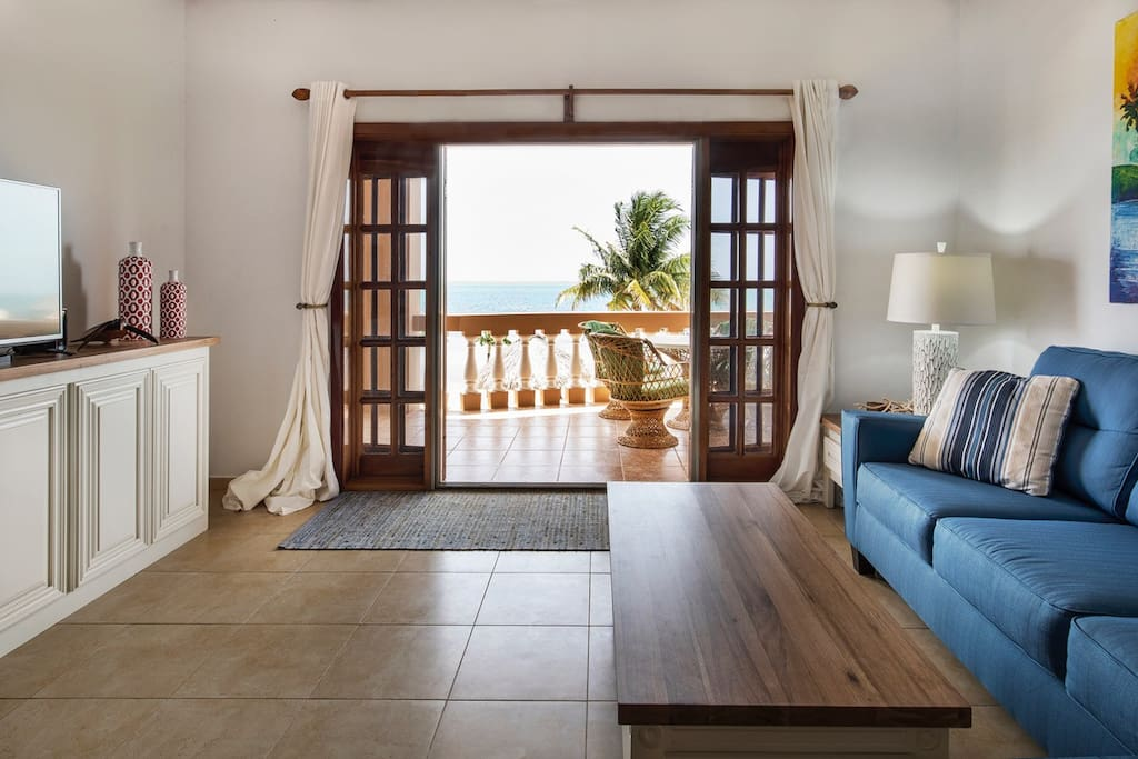 Living room with flatscreen TV, comfortable lounging furniture, and French doors to the oceanfront balcony!