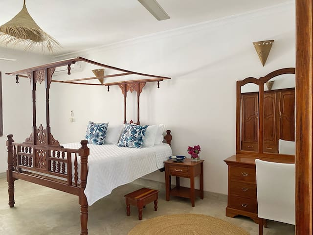 Bedroom 1 features a King size hand crafted Zanzibari-style bed, large wardrobe, dresser, hairdryer, AC, ceiling fan and love-seat. The bedroom leads out onto the main covered balcony. Mosquito nets are fitted on beds.