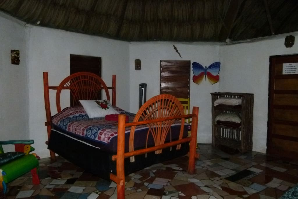 Interior of the Butterfly Cabana with queen bed, private bathroom with mosaic tile floor and maya thatch roof.