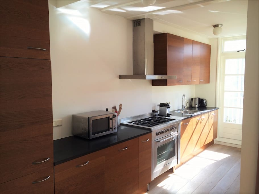 Modern kitchen with 5 burner gas stove and in-built fridge and dishwasher