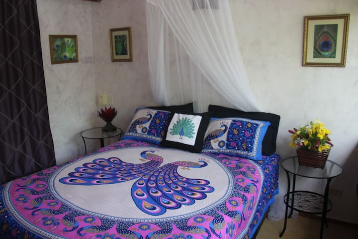 Queen bed with peacock theme.