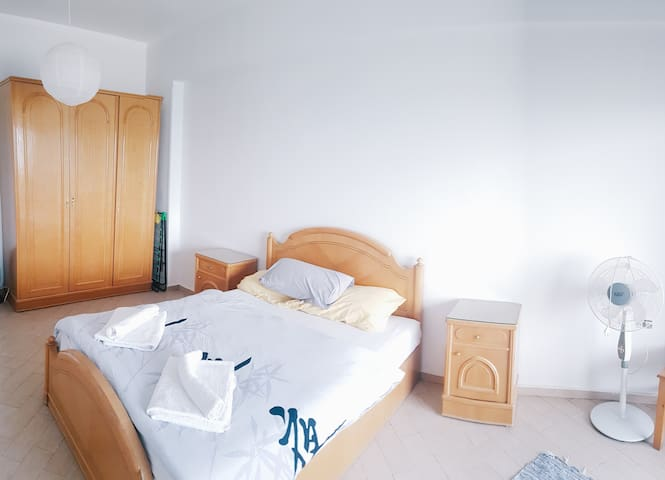 bright and comfortable bedroom with seaview direct  from cozy queen bed, Cosmetik table and mirror