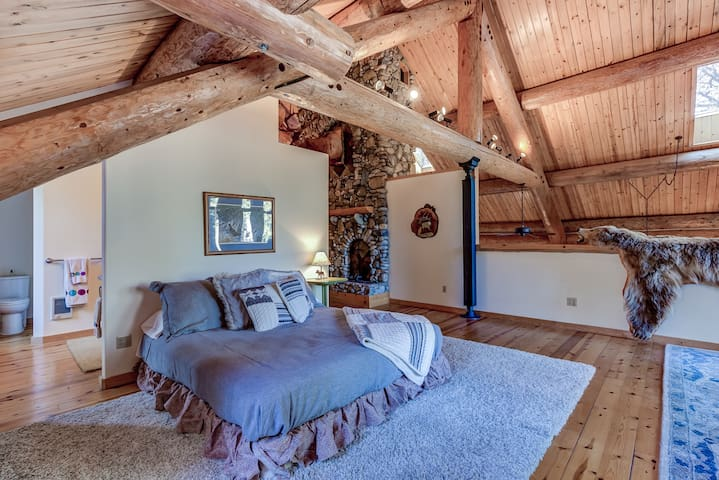 Master bedroom in loft offers a king bed and a wooden crib and attached master bathroom.