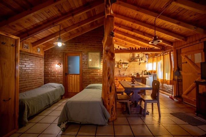 Vista de puerta de acceso, cocina comedor y a partir de la columna de troncos , dos sommiers y puerta que conduce a la sala de baño
