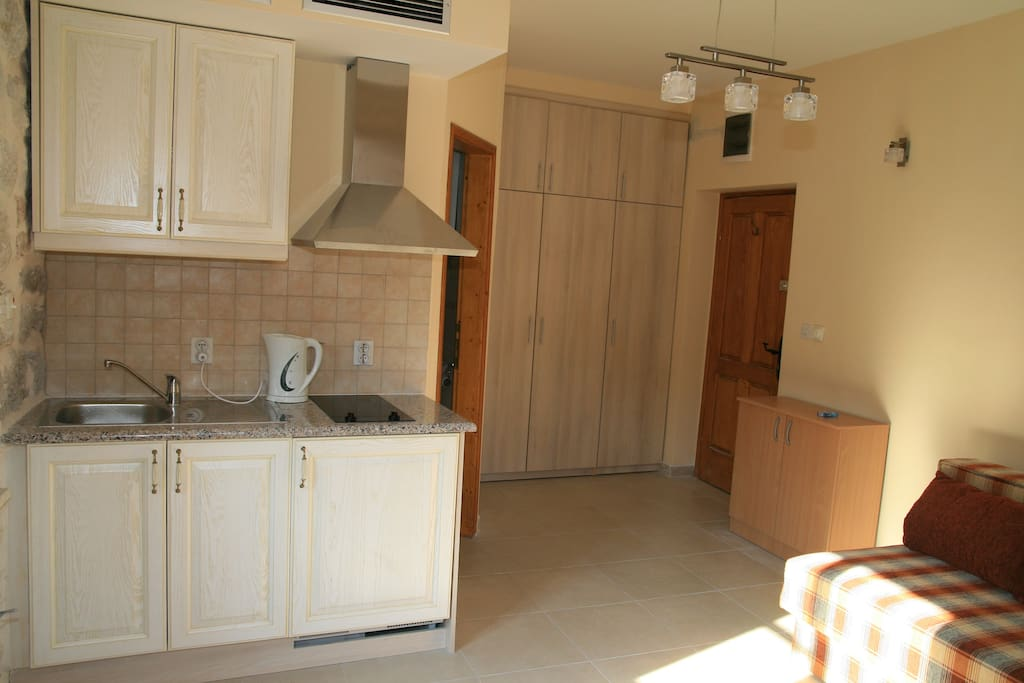 From window corner towards kitchenette, fitted wardrobe, front door to right, bathroom door centre