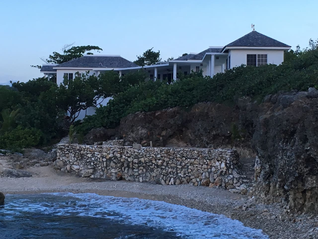 newly constructed traditional British colonial style home with detached cottage all on a cliff overlooking the private beach cove below