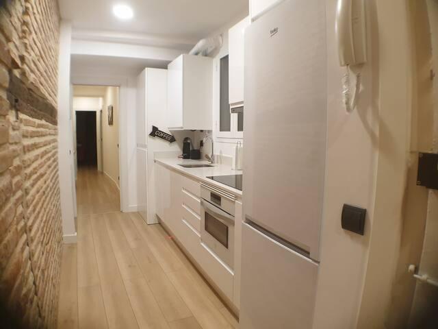 Cocina equipada con lavadora, secadora, horno, lavavajillas, frigorífico y cafetera.