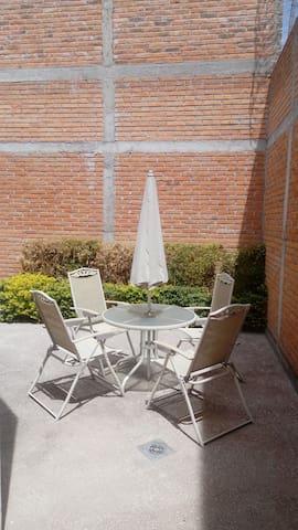 Terraza trasera #2 con mueble de jardín y jardinera.
