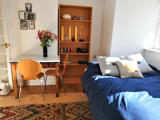 Main room with double bed, desk/table and TV
