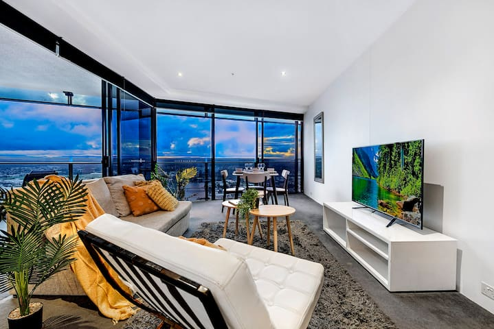 Living room opens onto a sun splashed balcony and stunning city views, with plenty of space to unwind for a memorable experience