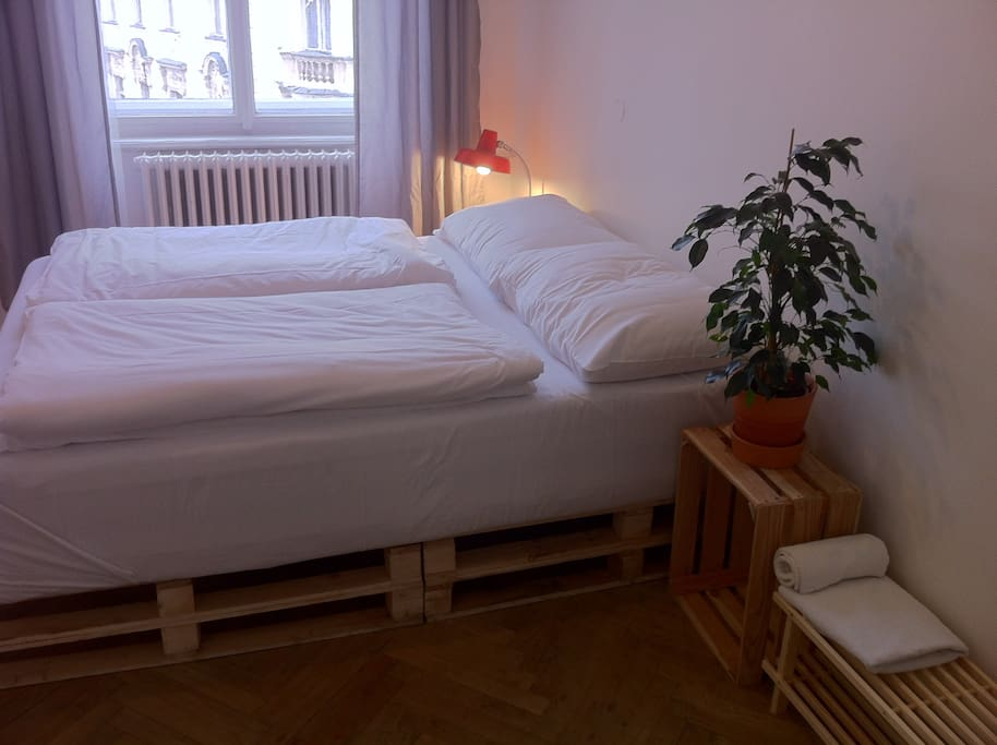 One queen-size bed and one double-size pallet bed (not pictured) in the room. Minimal design aesthetic, retro details.