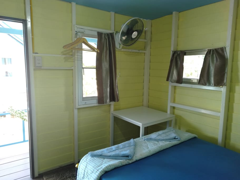 Our clean bright bungalow complete with a comfortable large double bed, a fan, a table for your laptop or other things and some hangers to hang your clothes.