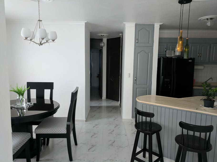 View from living room of common area with dining room to the left, kitchen to the right and bedrooms in the background