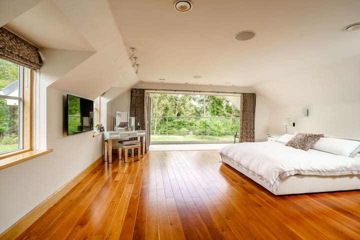 Master Suite with large balcony overlooking garden, super king bed, dressing table, chaise lounge & large en-suite bathroom with shower and bath. TV with Control 4 technology (music & TV), ac and under floor heating. Dressing room attached to bedroom