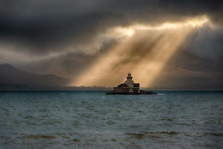 Fenit Lighthouse in Tralee Bay, overlooked by Mt Brandon.