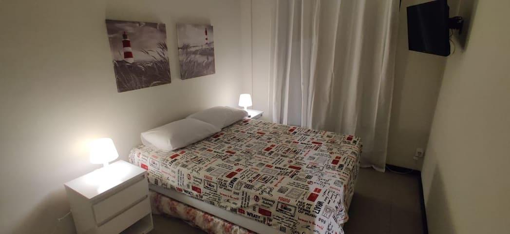 Quarto com cama de casal e cama auxiliar de solteiro. Ar condicionado e smart TV.