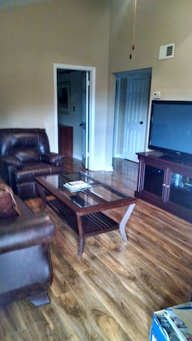 Living area with leather sofa, recliner and 52 inch TV.