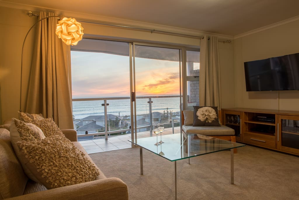 Open plan lounge, dining area leading to balcony with sea view