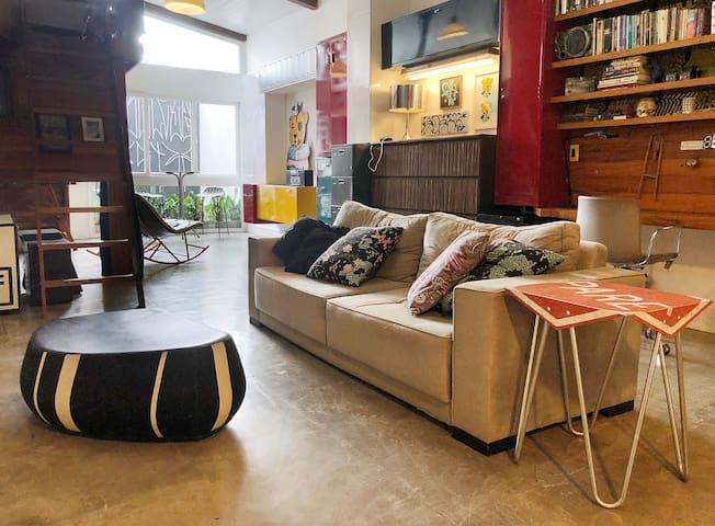 Vista da metade posterior do estúdio.  Sala de TV com sofá, almofadas, pouf e mesa feita com placa de trânsito. A televisão está na parede em frente ao sofá. Ao fundo bancada com duas cadeiras de couro para Home Office.