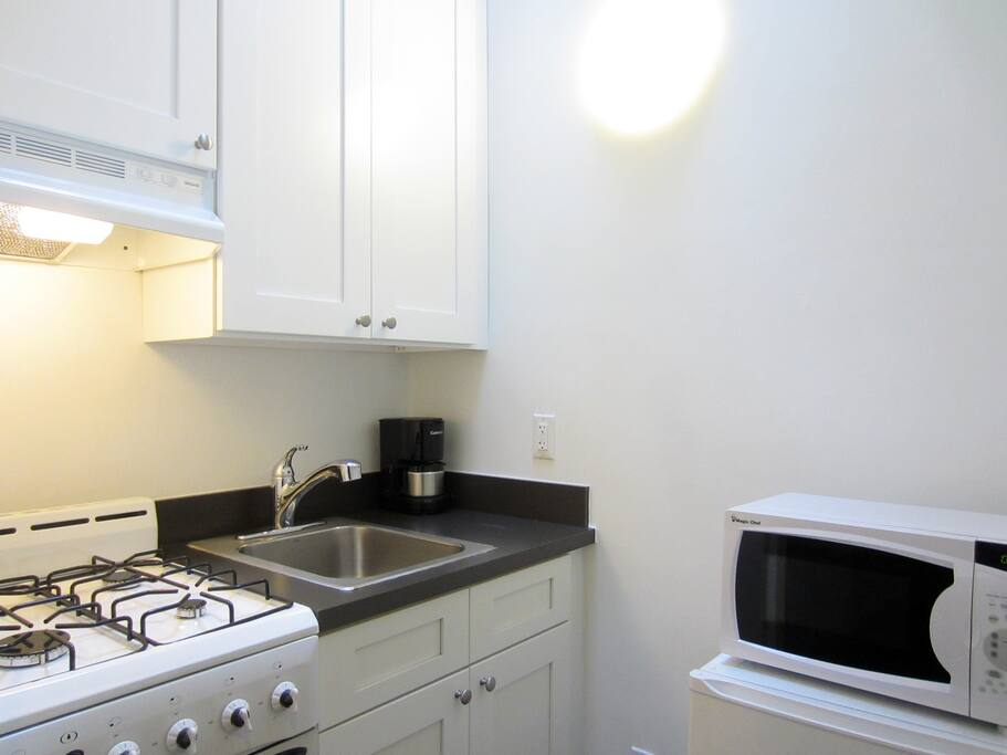 Stocked kitchen with gas range, a small refrigerator, and a microwave oven